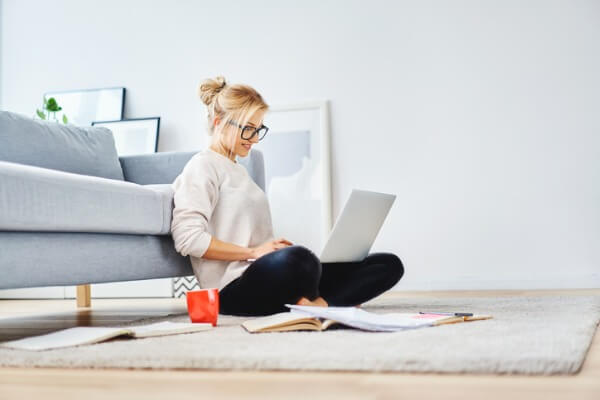 woman flexible working at home on floor